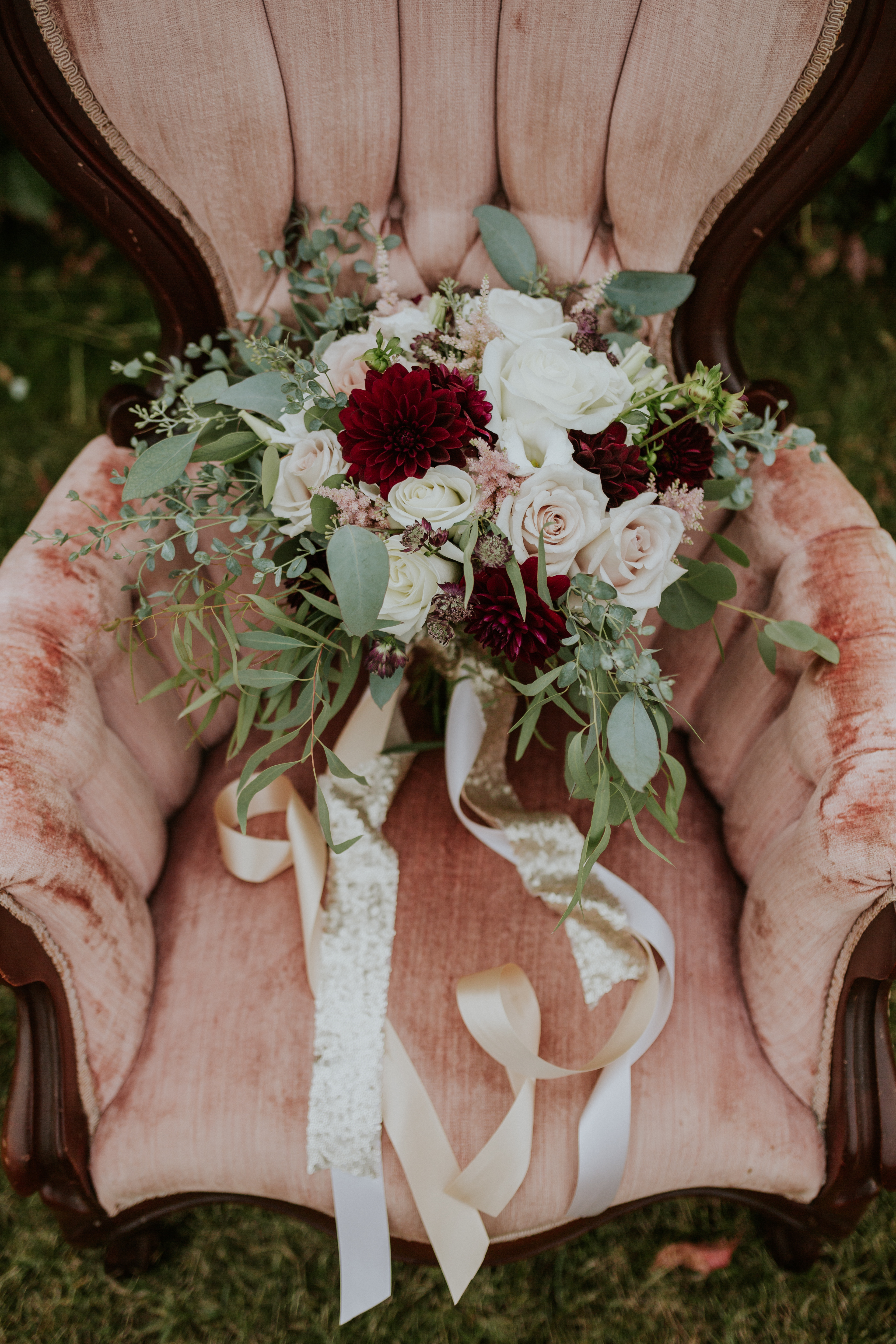CalyxFloralDbridal bouquet with trailing silk and sequin ribbons sitting on a dusty rose chair with burgundy dahlia, quicksand roses, burgundy astrantia, ivory roses and pale pink astilbe and eucalyptus