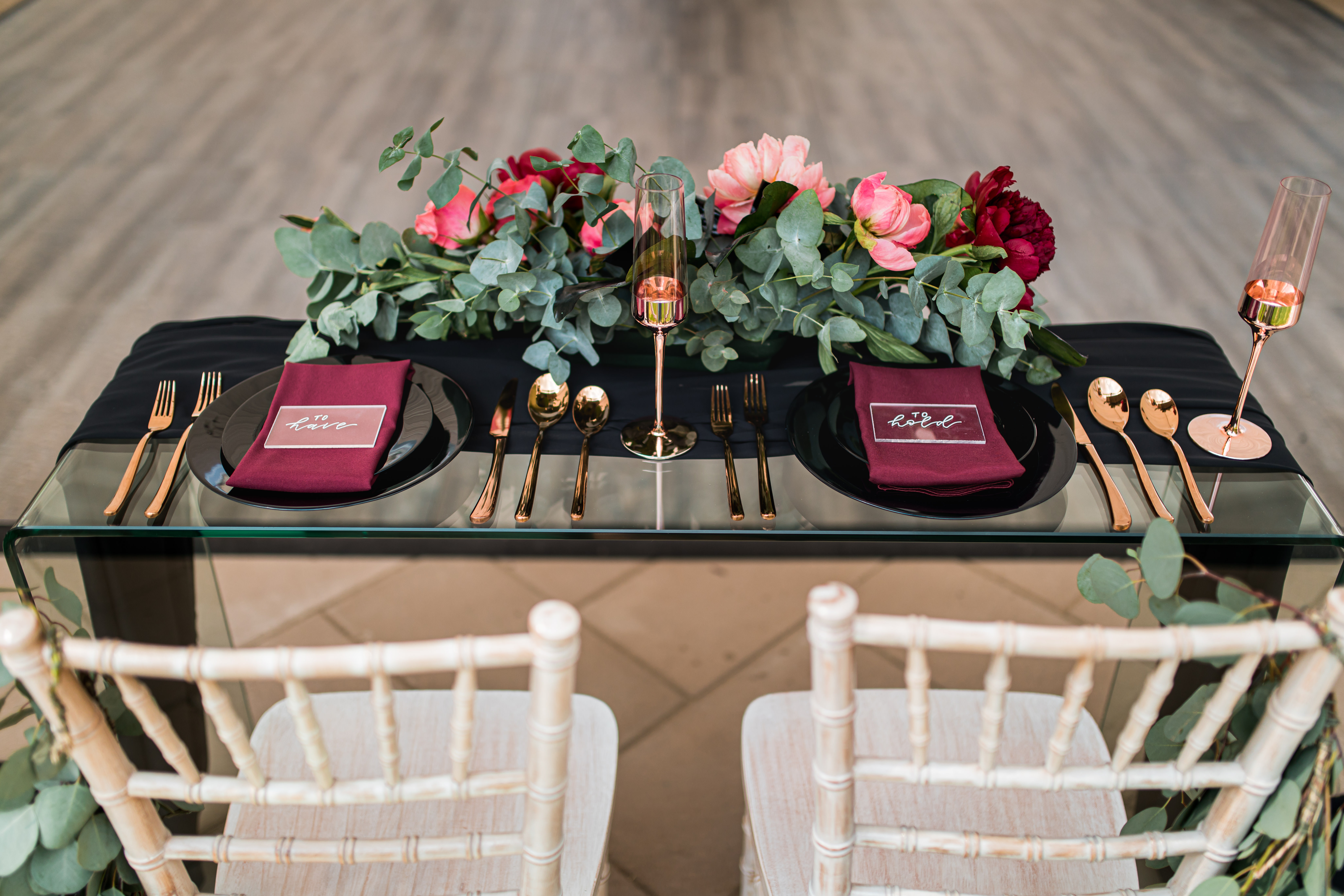 clear glass sweetheart table with limewash chiavari chairs, black dinnerware and gold wine glasses and cutlery with a floral arrangement of penies in coral and burgundy and cinerea eucalyptus