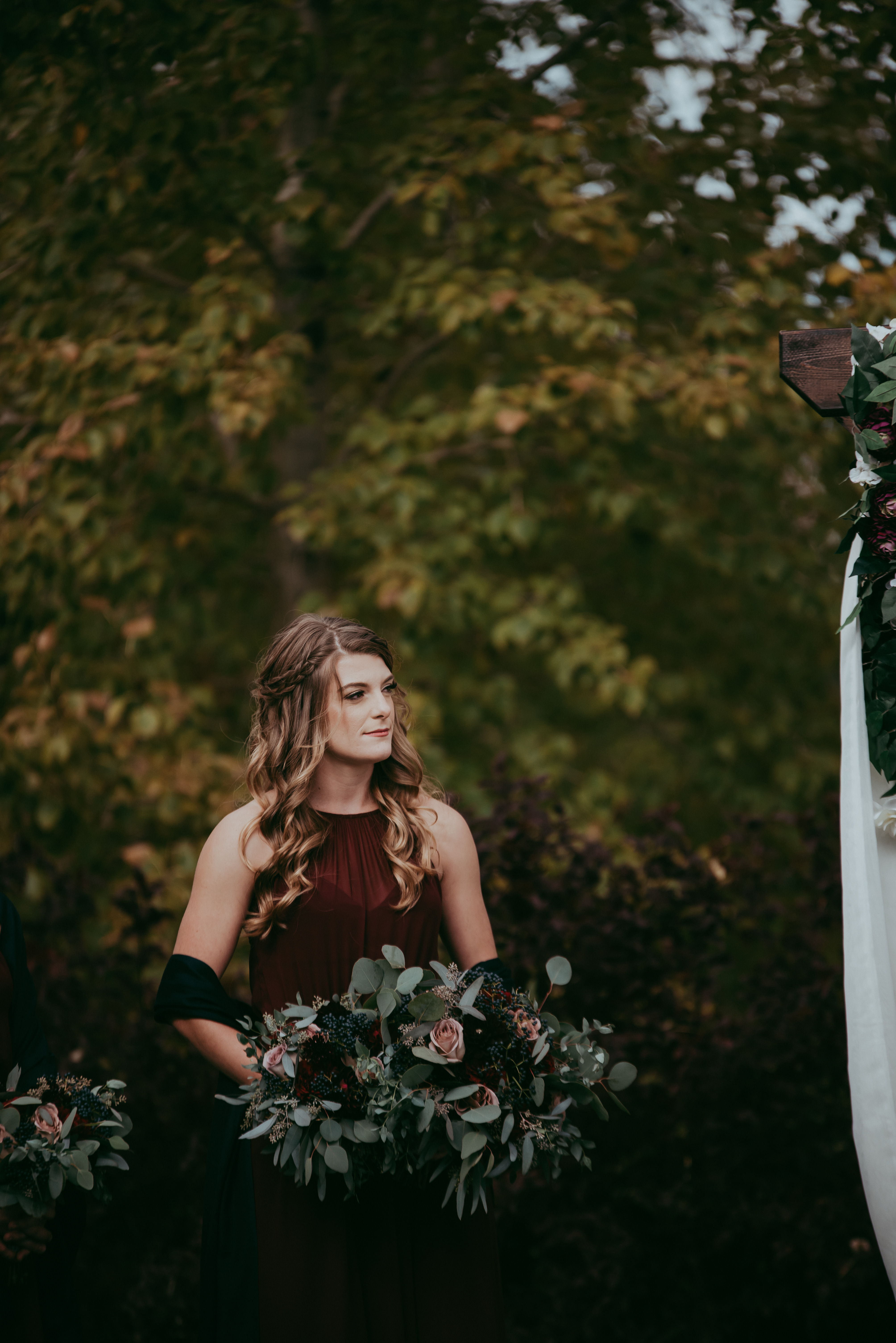bridesmaid standing beside rustic archway with burgundy dress and holding bouquets with red roses burgundy dahlias amnesia roses and navy viburnum berries and mixed eucalyptus