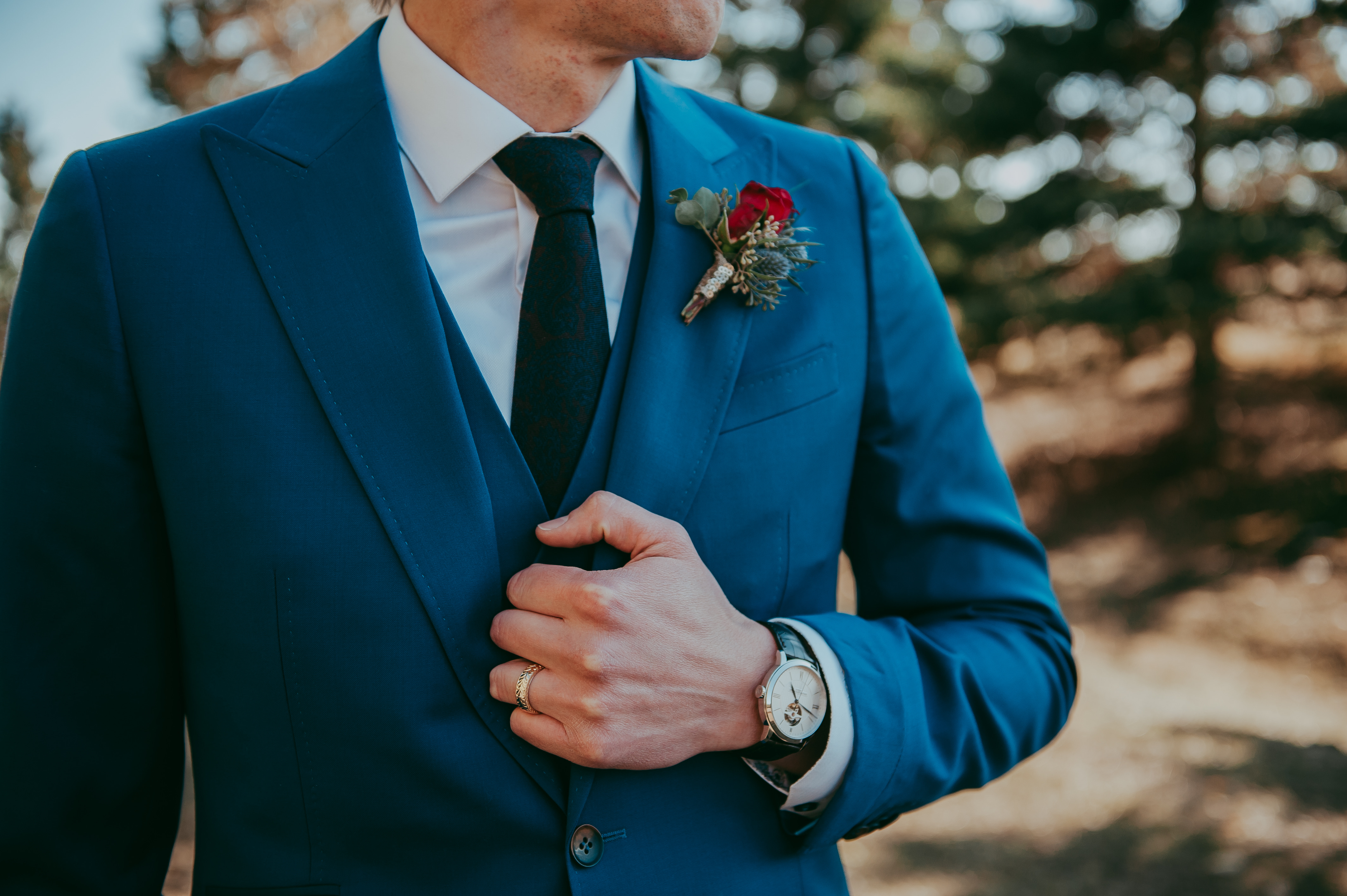 Groom in blue suit wearing a red rose and eryngium boutonniere and watch