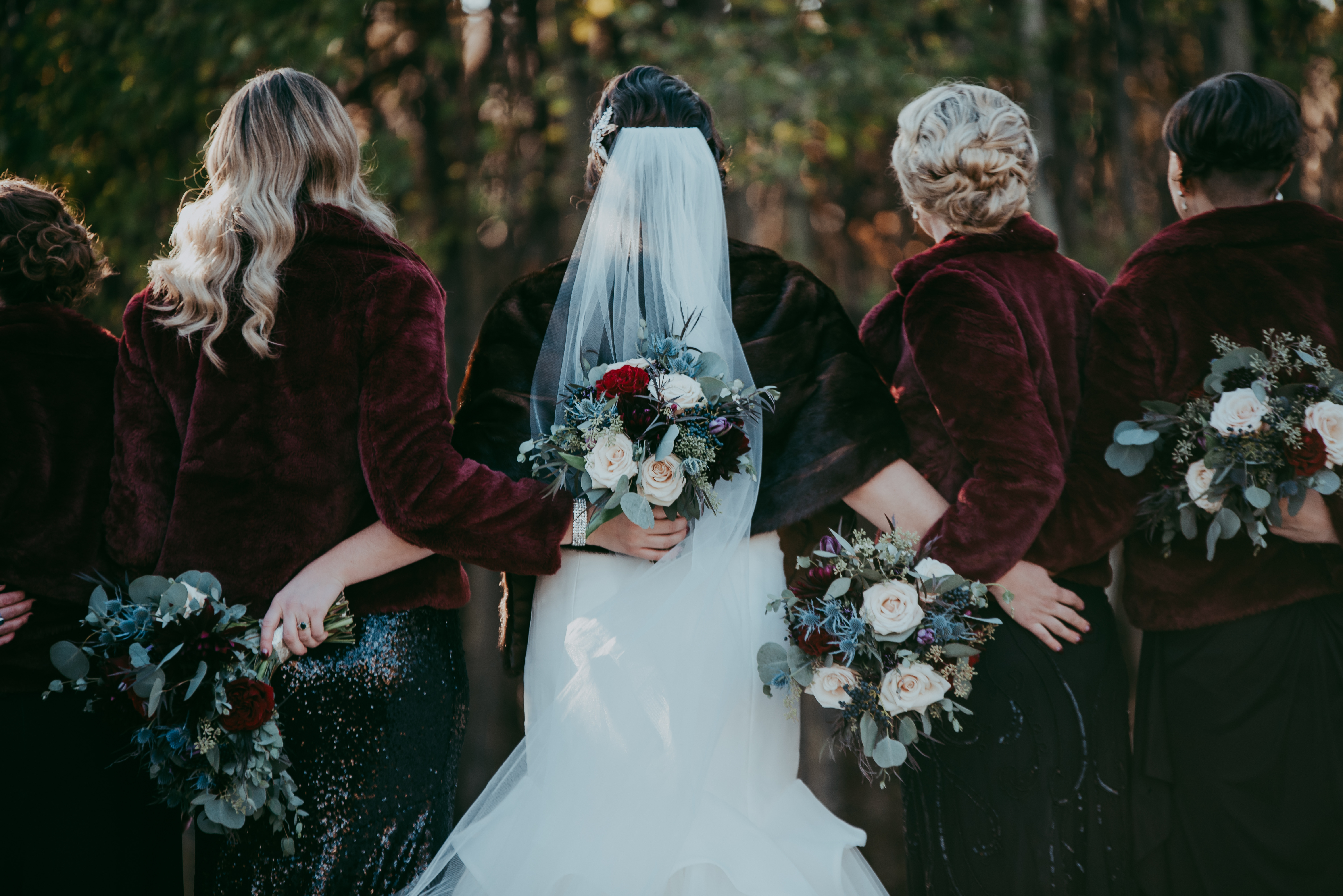 Fall bridal party picture from behind with fur coats and black sequin dresses bouquets with red roses quicksand roses eryngium and mixed eucalyptus retro bridal party