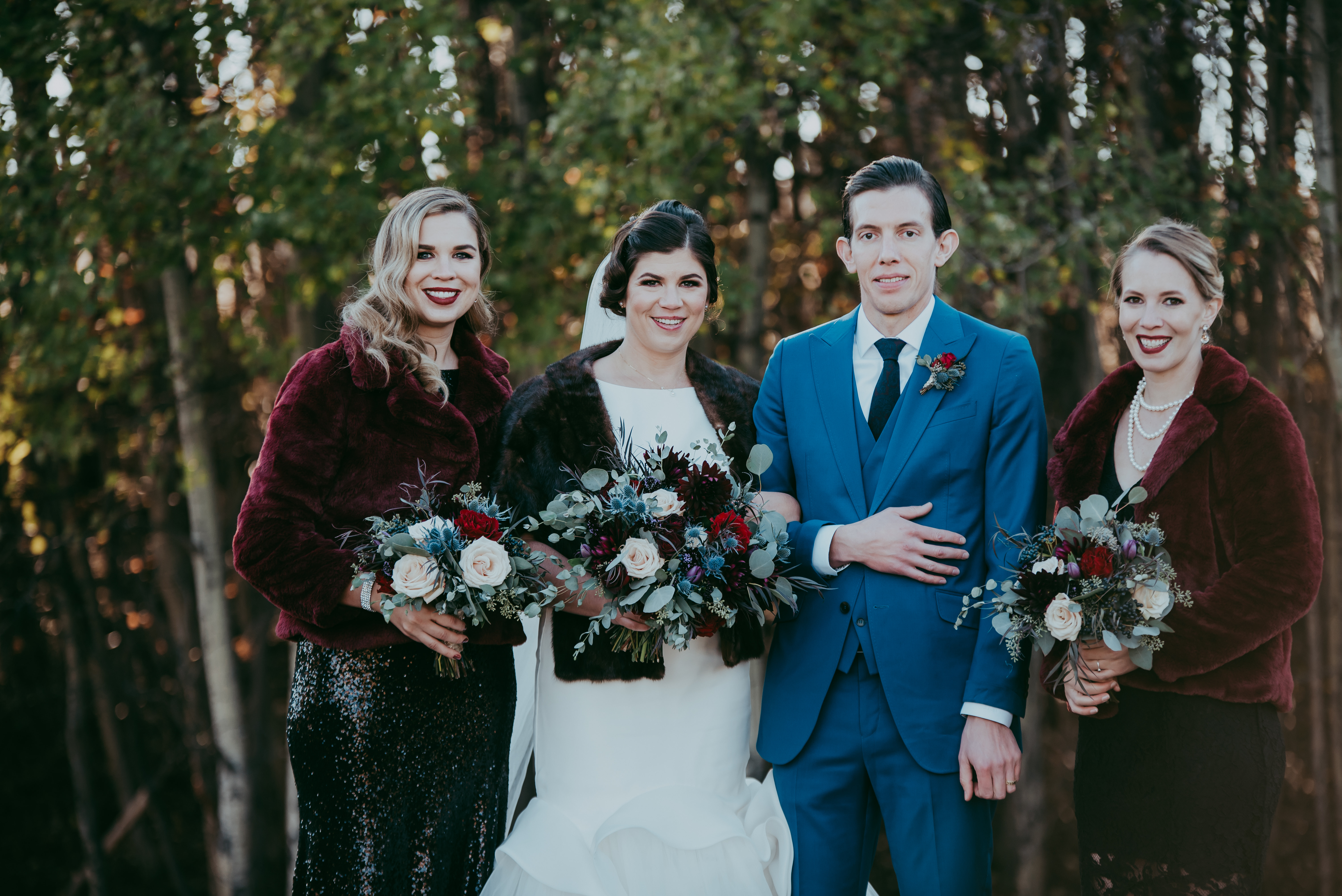 Fall bridal party picture with furn jackets and black sequin dresses groom in blue suit with red spray rose boutonniere bouquets with red roses, quicksand roses, burgundy dahlias and mixed eucalyptus