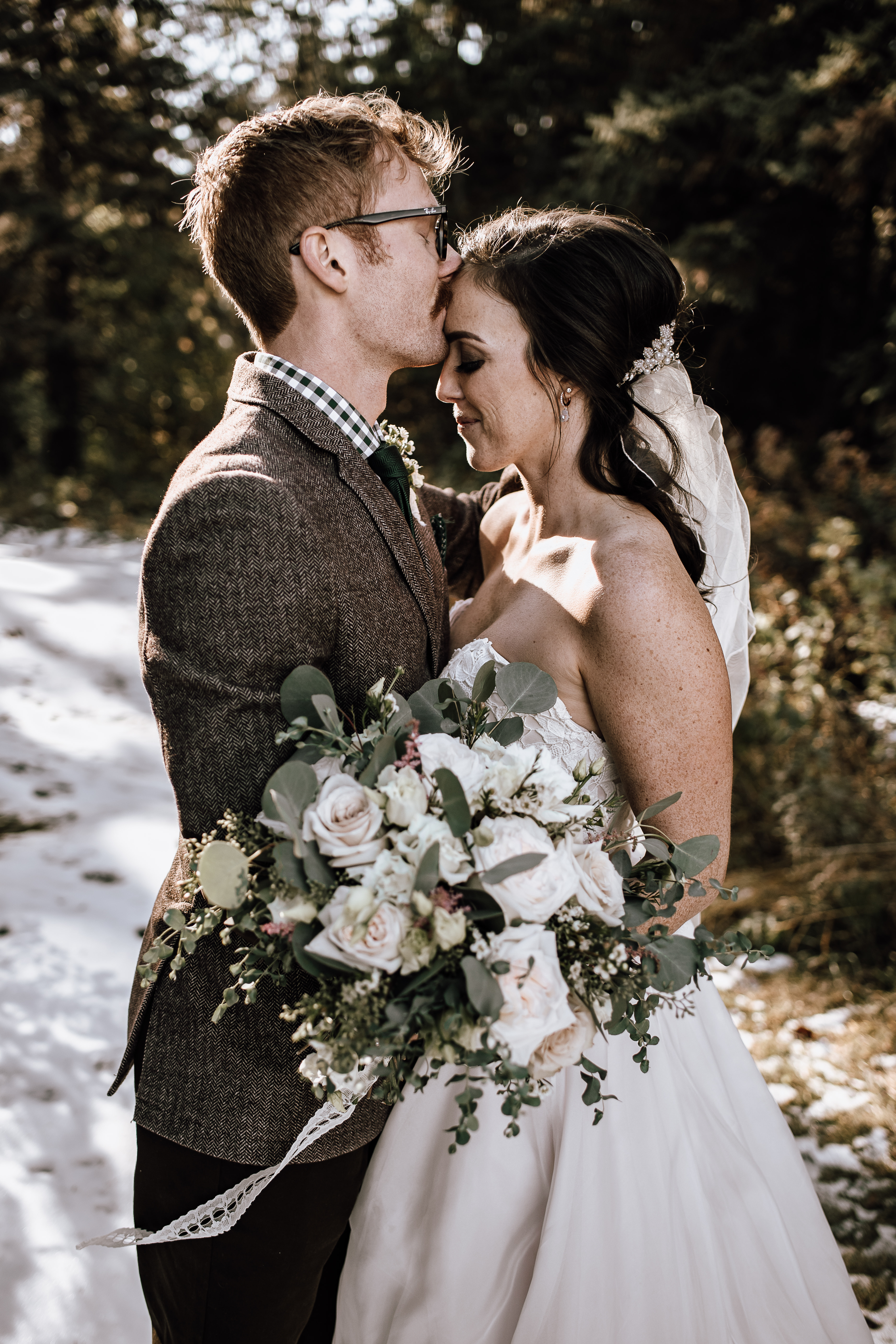 Groom kissing bride holding a white and blush bouquet with roses and eucalyptus