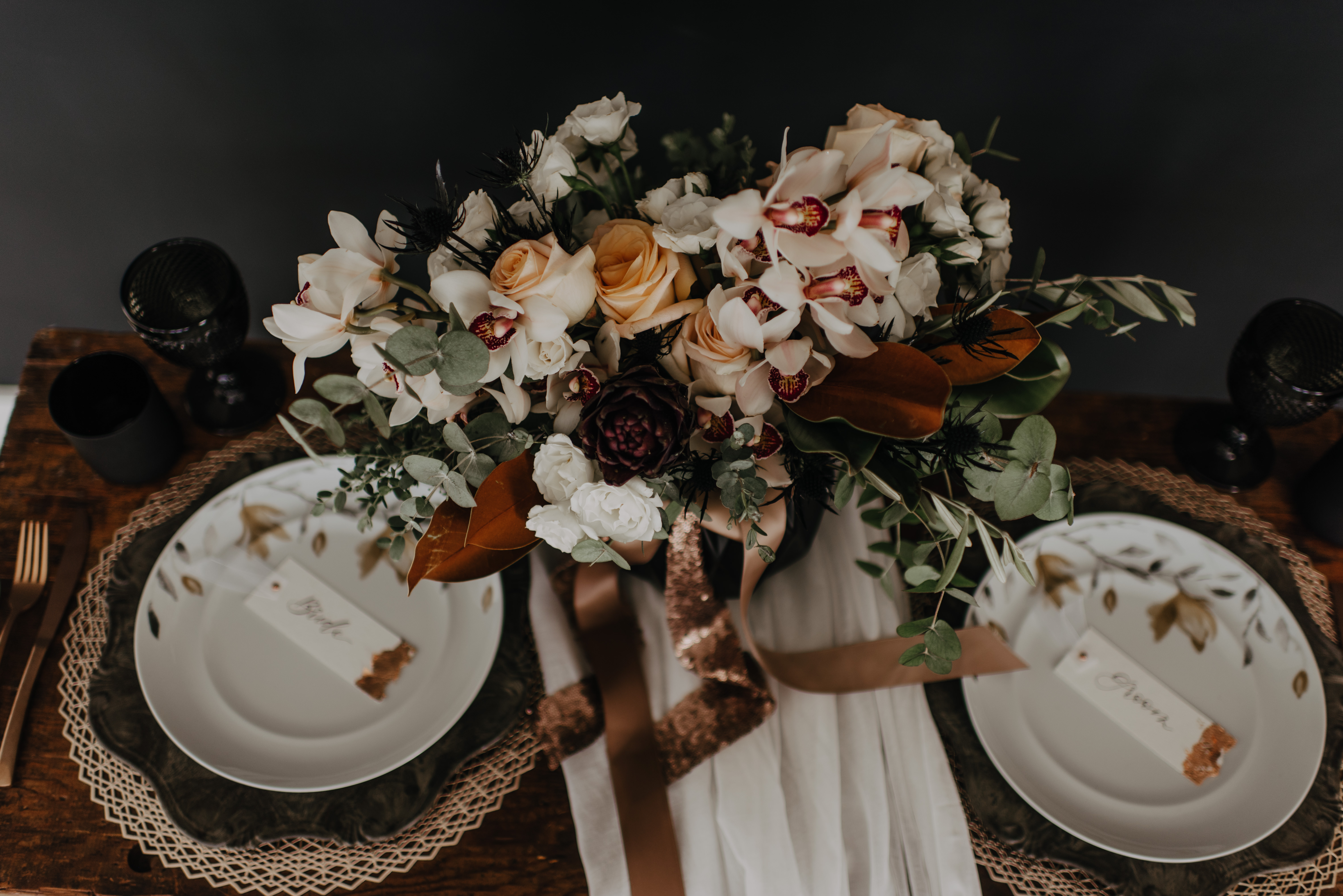 Neutrals Styled Shoot with Down the Aisle - Neutral coloured bridal bouquet with peach roses, orchids, magnolia leaves and eucalyptus greenery tied with trailing ribbon atop a decorated sweetheart table.